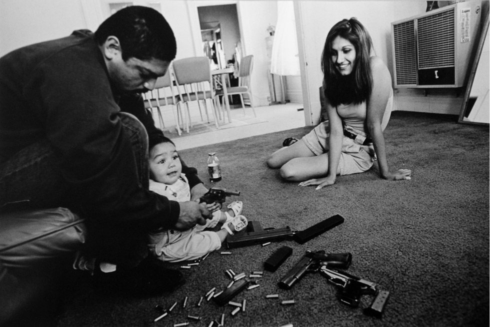 The morning after a rival gang tried to shoot Chivo for the fourth time, Chivo teaches his daughter how to hold a .32-caliber pistol. Her mother looks on.