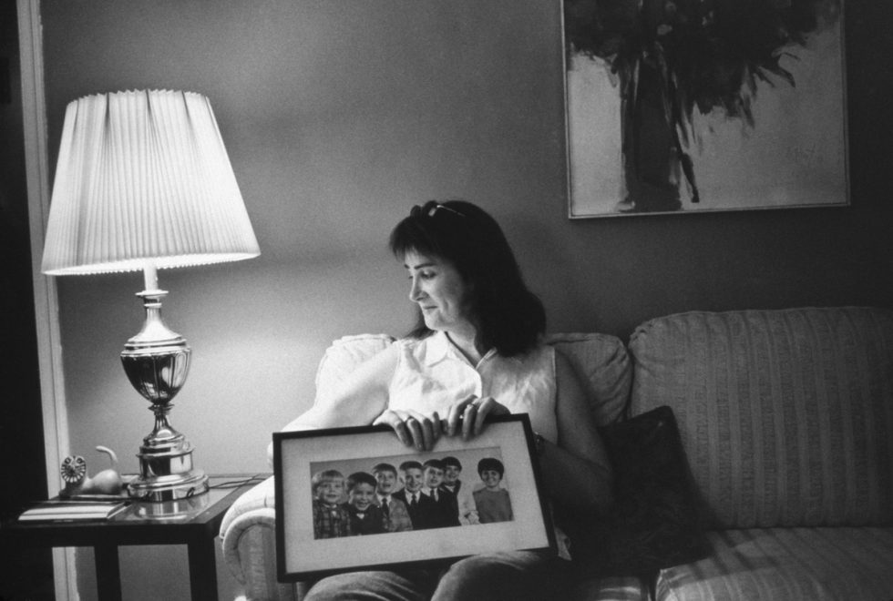 Mara Keisling, with an Early Family Portrait, in Her Mother's Living Room, Harrisburg, PA