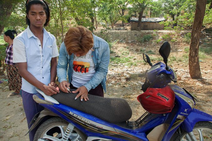 Mariette Pathy Allen, Myo Myo, a nat kadaw in Mandalay, polishes their nails on the seat of their motorcycle